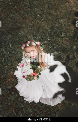 overhead view of beautiful young bride holding bouquet of flowers and looking at camera - Stock Photo