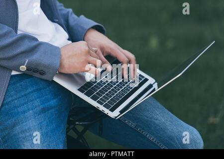cropped view of stylish man using laptop - Stock Photo