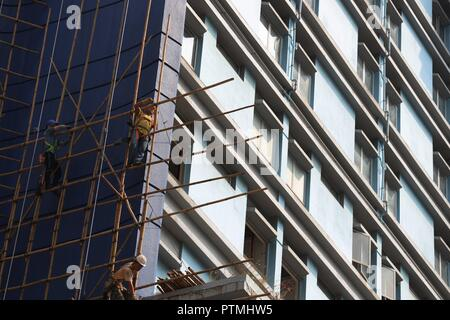 Hong Kong, CHINA. 10th Oct, 2018. Workers perform their duty skillfully on the bamboo scaffoldings outside the hotel awaiting to be demolished. Hong Kong is a place where Chinese traditional art of bamboo scaffoldings are being kept as a classic architectural heritage.Oct-10, 2018 Hong Kong.ZUMA/Liau Chung-ren Credit: Liau Chung-ren/ZUMA Wire/Alamy Live News - Stock Photo