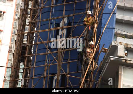 Hong Kong, CHINA. 10th Oct, 2018. Workers work skillfully on the bamboo scaffoldings outside the hotel awaiting to be demolished. Hong Kong is a place where traditional Chinese art of bamboo scaffolding is being inherited as a classic architectural craft.Oct-10, 2018 Hong Kong.ZUMA/Liau Chung-ren Credit: Liau Chung-ren/ZUMA Wire/Alamy Live News - Stock Photo