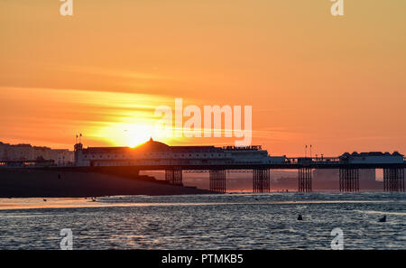Brighton UK 10th October 2018 - A beautiful sunrise and low tide on Brighton beach this morning as summer returns briefly with some areas of the south east expected to reach the mid twenties in temperature . However storms are forecast to spread across Britain on Friday Credit: Simon Dack/Alamy Live News - Stock Photo