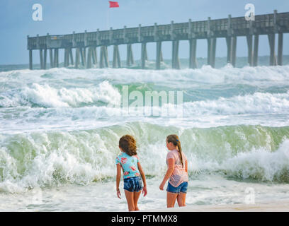 Pensacola Beach, Florida, USA. 9th Oct 2018. Jackie Knight and Kylee Wright, both 10, play in the water at Pensacola Beach pier as waves from Hurricane Michael churn up the Gulf, Oct. 9, 2018, in Pensacola Beach, Florida. Although red flags warned visitors to stay out of the water, that didn't stop them from gathering on the beaches across the Florida Panhandle to enjoy the surf. Hurricane Michael is expected to make landfall in Panama City, Oct. 10, 2018, as a category four hurricane.  Credit: Carmen K. Sisson/Cloudybright/Alamy Live News - Stock Photo
