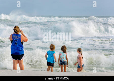 Pensacola Beach, Florida, USA. 9th Oct 2018. Chastity Pryor takes a photo while Piper Miller, 3; Jackie Knight, 10; and Kylee Reed, 10; stand in the surf at Pensacola Beach pier as waves from Hurricane Michael churn up the Gulf, Oct. 9, 2018, in Pensacola Beach, Florida. Although red flags warned visitors to stay out of the water, that didn't stop them from gathering on the beaches across the Florida Panhandle to enjoy the surf. Hurricane Michael is expected to make landfall in Panama City, Oct. 10, 2018, as a category four hurricane.  Credit: Carmen K. Sisson/Cloudybright/Alamy Live News - Stock Photo