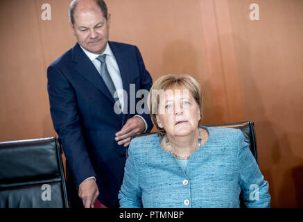 10 October 2018, Berlin: Federal Chancellor Angela Merkel (CDU) joins Olaf Scholz (SPD), Federal Minister of Finance, at the Federal Cabinet meeting at the Chancellery. Photo: Michael Kappeler/dpa - Stock Photo