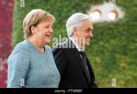 Berlin, Germany. 10th Oct 2018. 10 October 2018, Berlin: Federal Chancellor Angela Merkel (l, CDU) welcomes Sebastián Pinera, President of Chile, with military honours before the Federal Chancellery. Photo: Bernd von Jutrczenka/dpa Credit: dpa picture alliance/Alamy Live News - Stock Photo