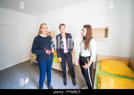 10 October 2018, Berlin: Viola Schröder (l-r), director of the emergency shelter for homeless families, Elke Breitenbach (Die Linke), senator for integration, labour and social affairs and Merle Mangels, social worker and deputy director of accommodation, stand in a room of the emergency shelter for homeless families. On Wednesday, the Berlin Senator for Integration, Labour and Social Affairs Breitenbach (Die Linke) visited Berlin institutions of homeless help. Photo: Arne Immanuel Bänsch/dpa - Stock Photo