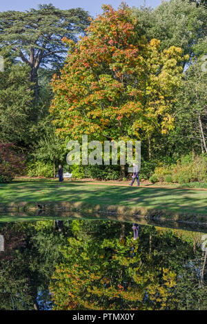 The Swiss Garden, Old Warden, Bedfordshire, UK. 10th October 2018. On another unseasonably warm day, visitors to the garden enjoy the first signs of Autumn colour reflected in the lake. Credit: David Humphreys/Alamy Live News - Stock Photo