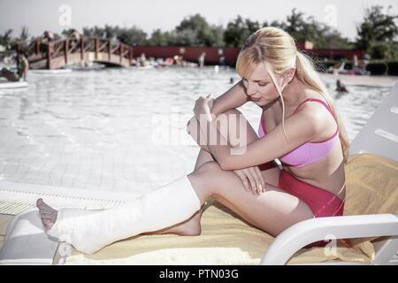Frau Jung Gipsbein Pool Sommer Urlaub Holiday Unfall Verletzung Beinbruch Bein Gips Behinderung Gehbehinderung Schicksal Situation Lebenslage Meistern - Stock Photo
