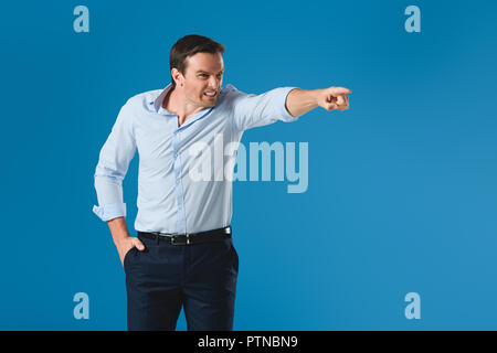 angry man standing with hand in pocket and pointing away with finger isolated on blue - Stock Photo