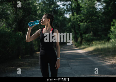 attractive sportswoman drinking water in park - Stock Photo