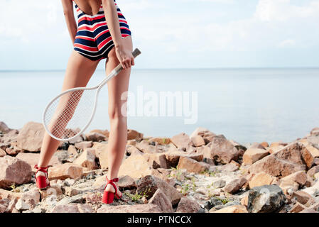 cropped view of young woman in striped swimwear holding tennis racket on rocky beach - Stock Photo