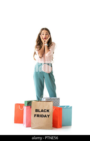 shocked young woman with shopping bags for black friday, isolated on white - Stock Photo