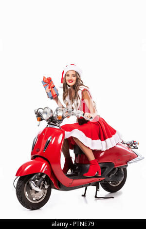 attractive happy girl in santa costume holding gift and driving red scooter, isolated on white - Stock Photo