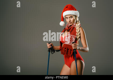beautiful woman in red swimming suit and santa claus hat with skiing equipment posing on grey backdrop - Stock Photo
