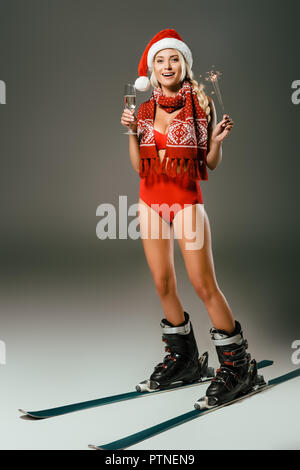 happy woman in santa claus hat with glass of champagne and sparkler in skiing boots on grey background - Stock Photo