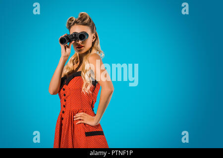 side view of fashionable pin up woman in retro style clothing with binoculars on blue background - Stock Photo