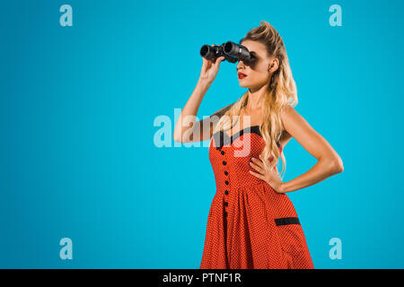 side view of fashionable woman in pin up style clothing with binoculars on blue backdrop - Stock Photo