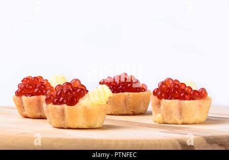 Tartlets with red caviar and butter on a cutting board - Stock Photo