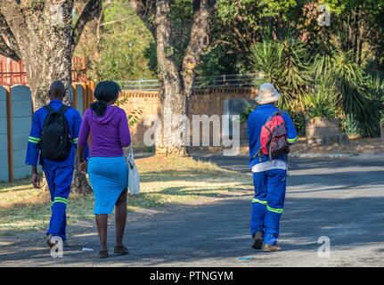 Johannesburg, South Africa - unidentified black people walk to their jobs through the streets of a residential suburb image with copy space - Stock Photo