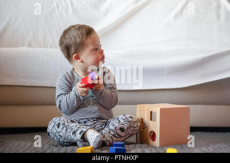 Portrait of cute boy with Down syndrome playing in home - Stock Photo