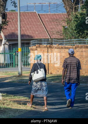 Johannesburg, South Africa - unidentified black South African couple walk through the streets of a residential suburb image with copy space - Stock Photo