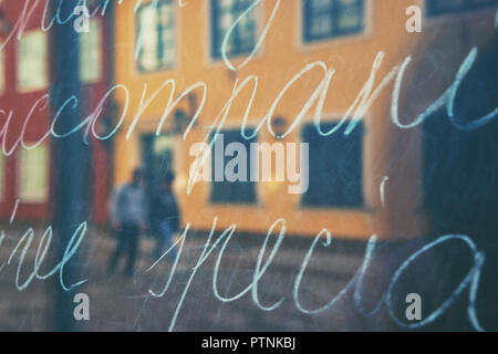 City in reflection of a storefront with text - Stock Photo