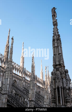 Photo taken high up on the terraces of Milan Cathedral / Duomo di Milano, Italy, showing the gothic architecture in detail against a clear blue sky. - Stock Photo