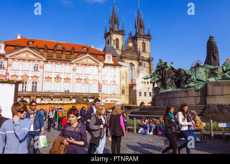 Prague, Czech Republic : Tourists at the Old Town Square stand by the Jan Hus Memorial designed by Ladislav Šaloun in 1915 with the Church of Our Lady - Stock Photo