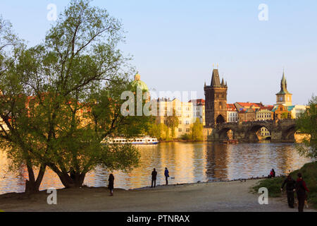 Prague, Czech Republic : Tourists walk at sunset by the shore of the Vltava river by the Charles Bridge. - Stock Photo