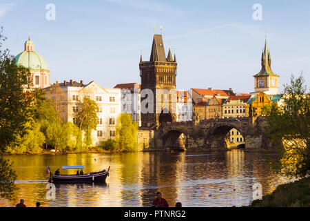 Prague, Czech Republic : A sightseeing boat full of tourists sails towards Charles Bridge at sunset. - Stock Photo