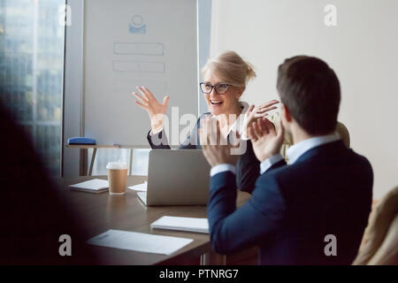 Employees applaud congratulating female boss with success - Stock Photo