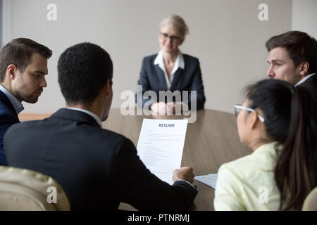 Back view of millennial employers consider candidate resume - Stock Photo
