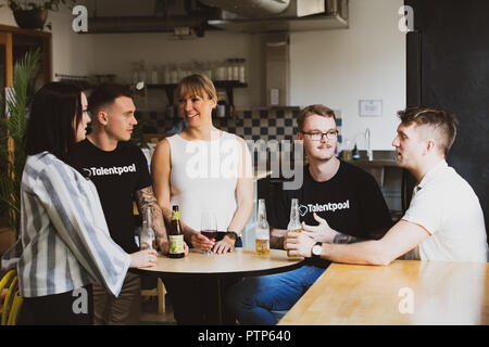 Businesspeople relax after a hard day's work with a few drinks in a co-working space - Stock Photo