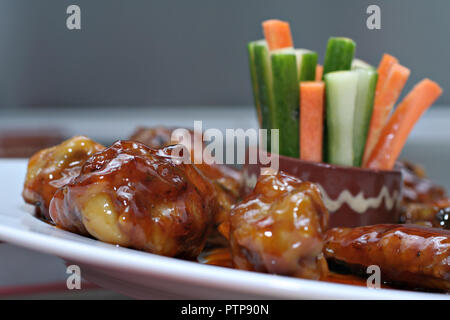 Close-up of chicken wings in barbeque sauce with vegetable sticks zucchini and carrot - mexican cuisine - Stock Photo