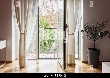 Modern apartment view through open glass  terrace door looking at trees - Stock Photo