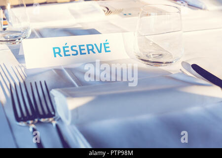Reserved Table. A tag of reservation placed on the wood table. Reserved logo. Reservation sign. Paper tag with reservation logo. Reserved table in a r - Stock Photo