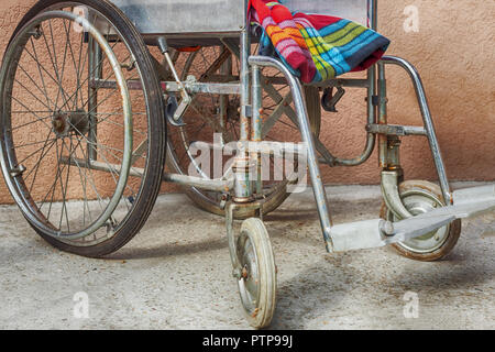 Empty old wheelchair with colorful blanket waiting for the sick patient - detail - Stock Photo