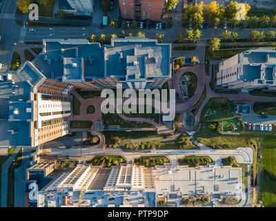 Aerial top view to the courtyard surrounded by tall houses with skyscrapers with pedestrian paths and a green grass lawn forming a closed area for liv - Stock Photo