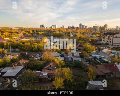 Autumn landscape on the city from the side of the ghetto with old dilapidated houses on the background of high multi-storey skyscrapers in the center  - Stock Photo