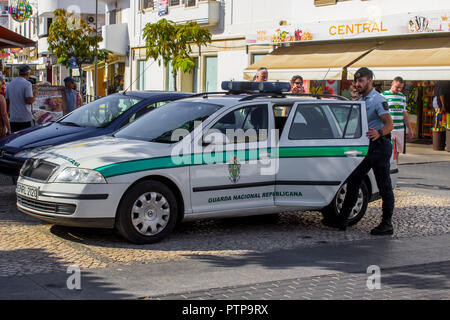 28 September 2018 A Portuguese National Guard policeman entering a car parked in in the shade outside the local Police Station in Albuferia Portugal - Stock Photo