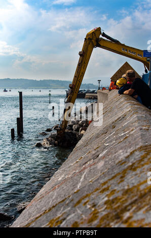 EXMOUTH, DEVON, UK - 05OCT2018:  Large boulders are placed at in front of the sea wall near Exmouth Docks in order to strengthen the sea defences. - Stock Photo