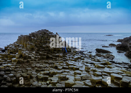 Tourists walking on the famous Giants' Causeway stones in Northern ireland - Stock Photo
