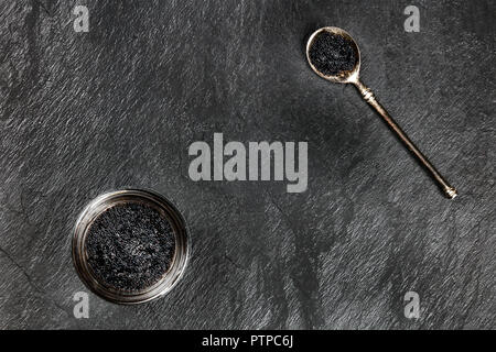 An overhead photo of black caviar in a jar and in a spoon, shot from above on a black background with copyspace - Stock Photo