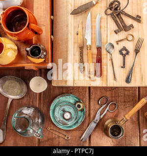 An overhead photo of many vintage objects, flea market stuff on a wooden background - Stock Photo