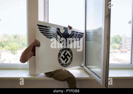 Belarus, Gomel. May 9, 2018. Victory Day. Reconstruction take Reichstag.Russian soldier throws out a poster with a German swastika - Stock Photo