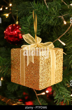 Vertical Photo of Gold Glitter Square Gift Box with Shiny Ribbon Bow Ornament for Christmas Decoration - Stock Photo
