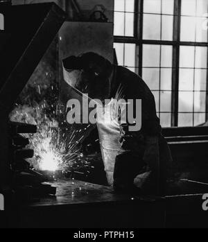 Welder at the factory in a welding mask welds metal parts, welding and sparks, black and white, welding holder - Stock Photo