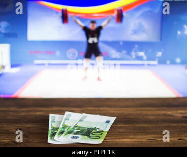Euro money on the background of TV on which show weightlifting, sports betting, bookmaker - Stock Photo