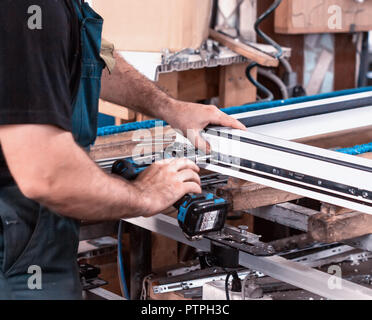Production windows pvc, man screwed screwdriver hinged defense on the sash pvc frame, close-up, work - Stock Photo