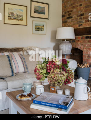 Hydrangeas on coffee table with books and cups in 18th century Norfolk cottage - Stock Photo